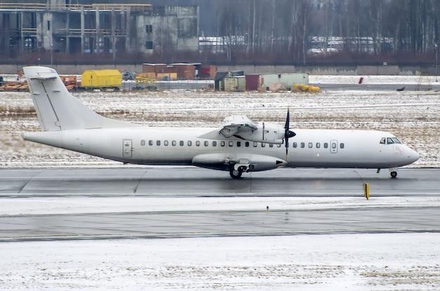 Pequeno avião de passageiros no aeroporto no inverno, com neve ruim e nevasca.
