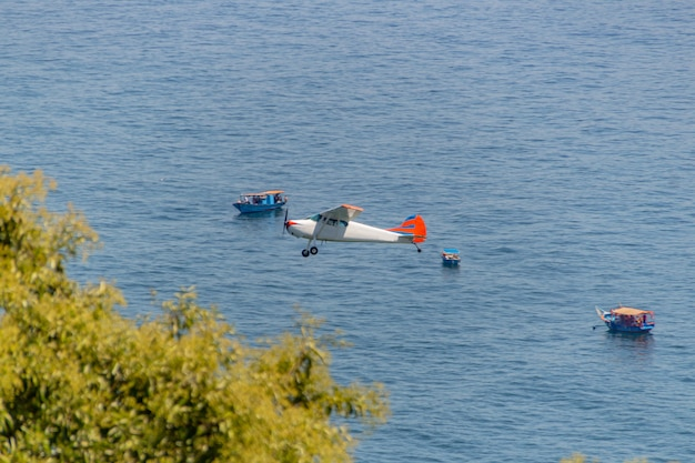 Pequeno avião sobrevoando a praia de copacabana, no rio de janeiro.