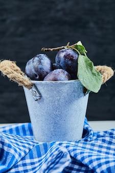 Pequeno balde de ameixas de jardim no escuro com toalha de mesa.