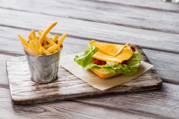 Pequeno balde de batatas fritas. pão com alface e queijo. produtos alimentares frescos. receita com ingredientes simples.