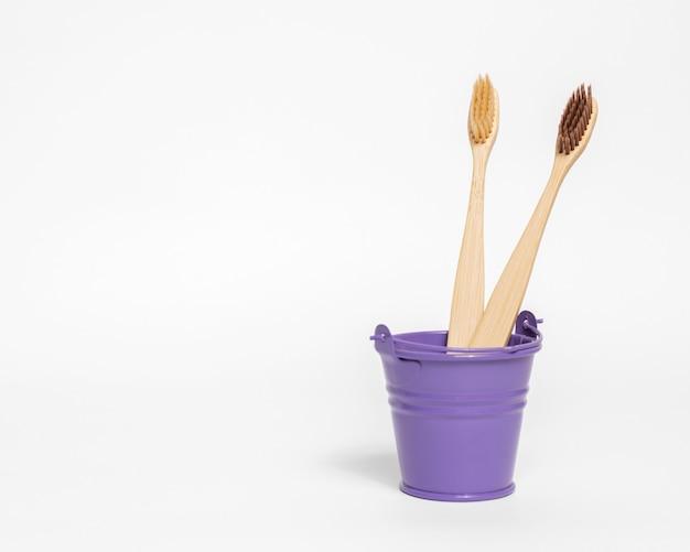 Pequeno balde roxo com escovas de dente de bambu em fundo branco