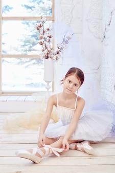 Pequeno balé prima. a jovem bailarina está se preparando para uma apresentação de balé. menina em um vestido de baile branco e pointe perto da janela, lindo cabelo ruivo. jovem atriz de teatro