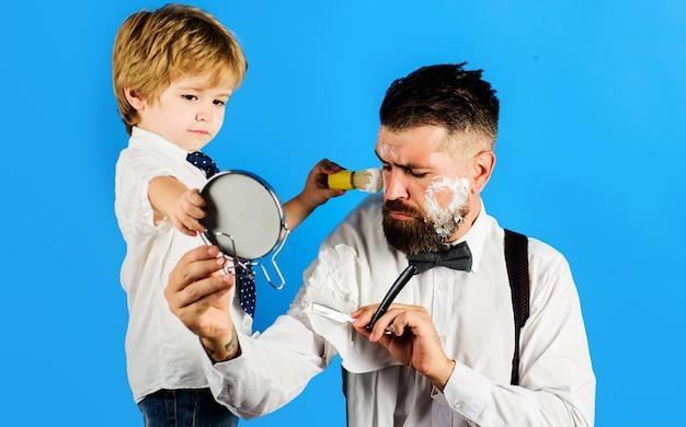 Pequeno barbeiro. assistente para o pai. dia dos pais. filho segura espelho para o pai.