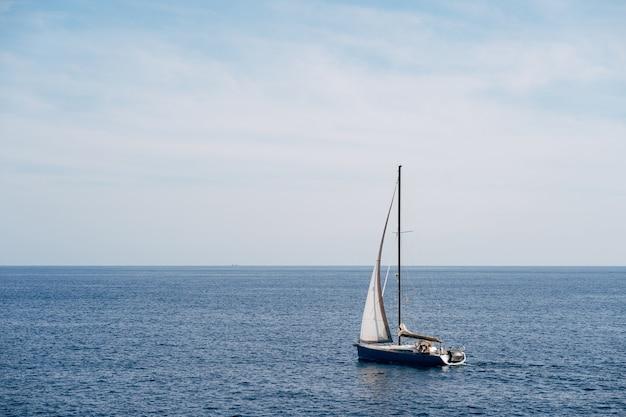 Pequeno barco com uma vela branca esvoaçante ao vento, navega no mar