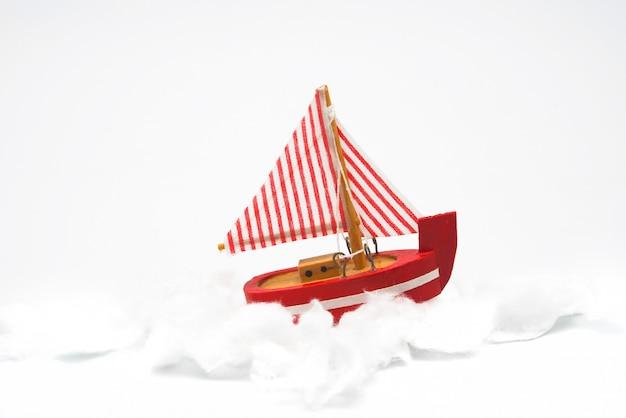 Pequeno barco de brinquedo de madeira, feito à mão, isolado no branco