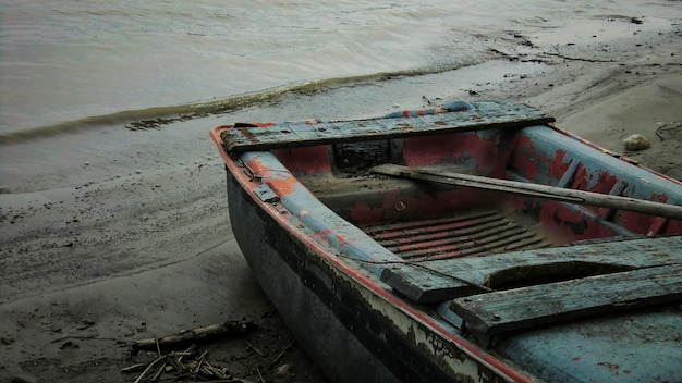 Pequeno barco de madeira destruído e gasto pelo tempo e pelo tempo, abandonado nas margens de um rio na itália.