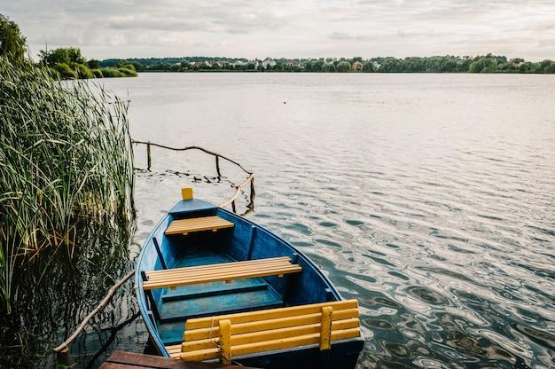 Pequeno barco de pesca de madeira ou barco turístico no lago na água em uma baía isolada em um dia ensolarado.