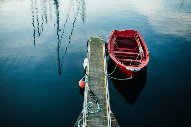 Pequeno barco de pesca vermelho em um mini porto