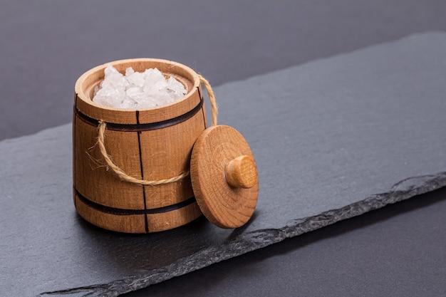 Pequeno barril de madeira para guardar o sal e uma tábua de corte em fundo preto. vista do topo.
