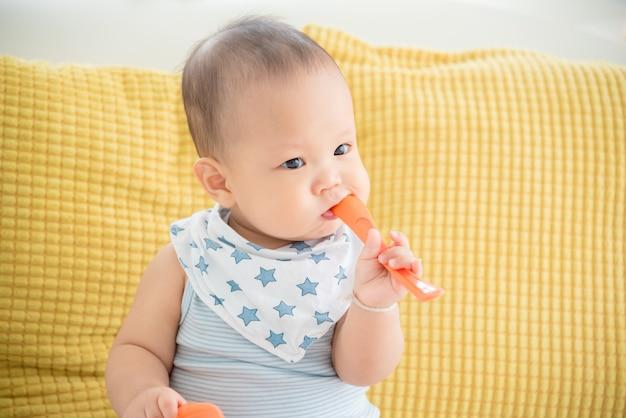 Pequeno bebê asiático sentado e morde a colher de plástico após a refeição terminada