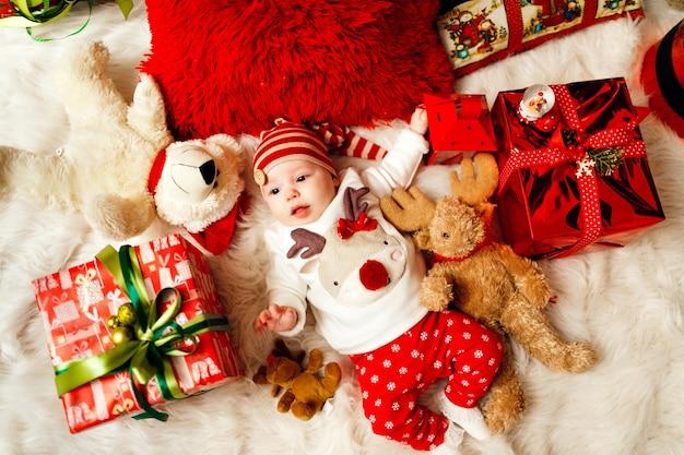 Pequeno bebê com roupas vermelhas e brancas está entre presentes de natal e brinquedos no chão