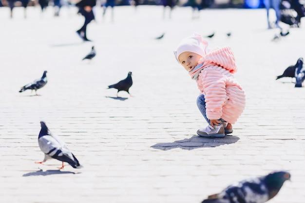 Pequeno bebê fofo andar na praça com pássaros