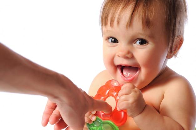 Pequeno bebê segura mordedor de mão, mordidas de bebê brinquedo de dentição