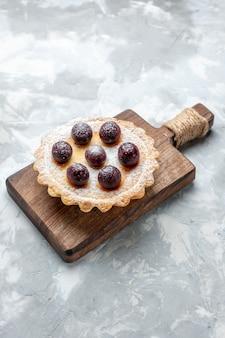 Pequeno bolo com cerejas e açúcar em pó na luz, bolo biscoito doce de frutas