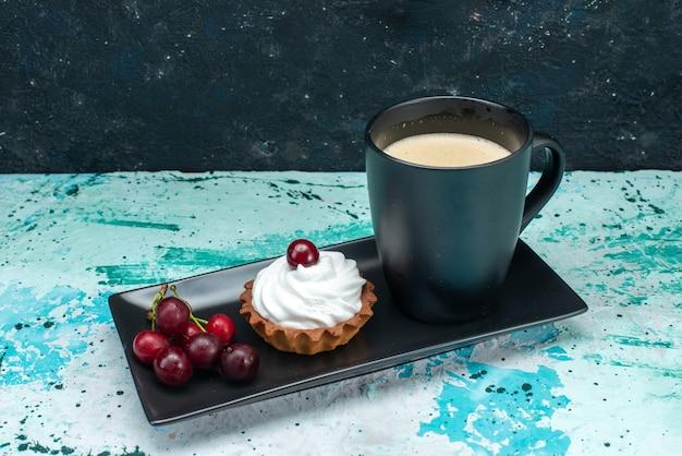 Pequeno bolo com creme e cerejas junto com leite em azul escuro, torta de bolo de frutas creme doce
