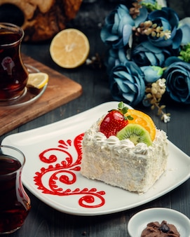 Pequeno bolo cremoso branco decorado com morango, laranja, kiwi