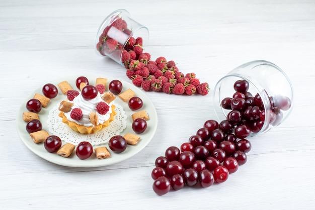 Pequeno bolo cremoso com cerejas ácidas e framboesas no branco, doce de bolo de frutas frescas