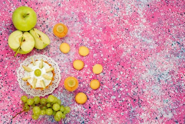 Pequeno bolo cremoso com fatias de frutas, biscoitos, uvas na mesa colorida, bolo doce com açúcar cor de assar