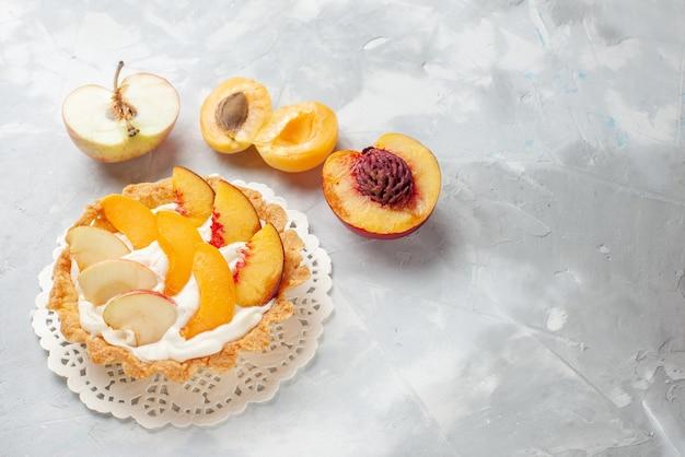 Pequeno bolo cremoso com frutas fatiadas e creme branco junto com damascos frescos, pêssegos em uma mesa com luz branca, bolo de frutas biscoito assado