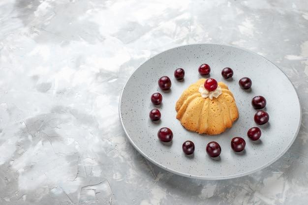 Pequeno bolo delicioso com cerejas dentro do prato cinza, bolo biscoito doce açúcar