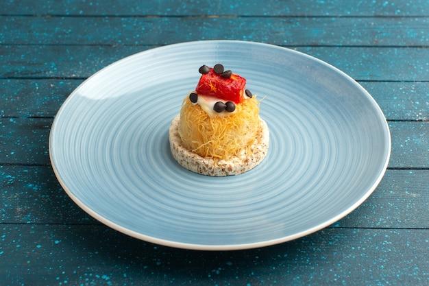 Pequeno bolo delicioso com creme e geléia por cima dentro do prato azul