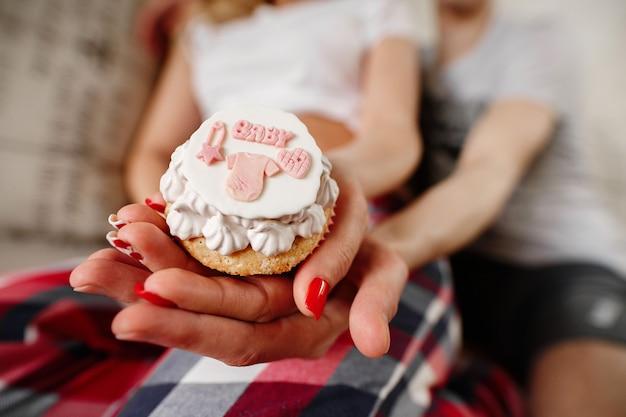 Pequeno bolo para uma menina recém-nascida. os futuros pais esperando bebê. família jovem em antecipação ao parto.
