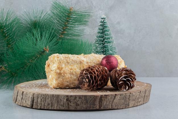 Pequeno bolo rolo ao lado de enfeites de natal em uma placa de madeira com fundo de mármore.