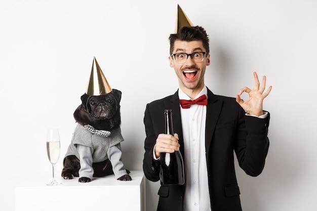 Pequeno cachorro preto usando chapéu de festa e parado perto de um homem feliz comemorando o feriado. proprietário mostrando sinal de ok e segurando uma garrafa de champanhe, fundo branco