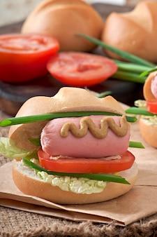 Pequeno cachorro-quente alegre com salsicha e tomate