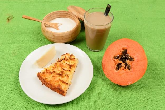 Pequeno café da manhã brasileiro com café com leite, queijo, mamão e torta de mandioca