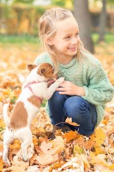 Pequeno cão de raça pura com uma menina caucasiana