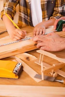 Pequeno carpinteiro habilidoso. menino sério fazendo medições na prancha de madeira enquanto o pai o ajudava