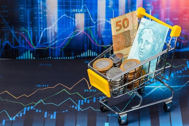 Pequeno carrinho de compras com moedas e notas de 50 e 100 reais simbol do mercado financeiro brasileiro