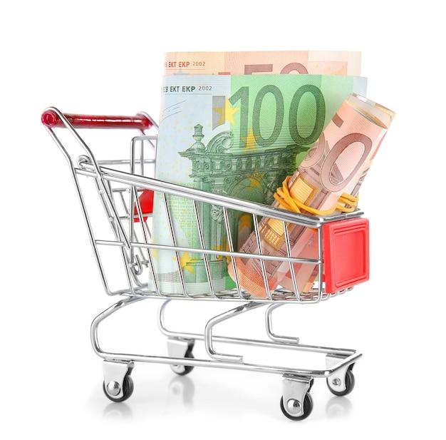 Pequeno carrinho de compras com notas de euros isoladas em branco