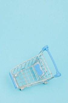 Pequeno carrinho de compras no fundo azul