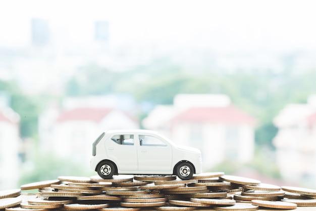 Pequeno carro sobre um monte de moedas empilhadas de dinheiro, para conceito de financiamento de custos de empréstimos. com filtro tons efeito vintage retro, tons quentes.