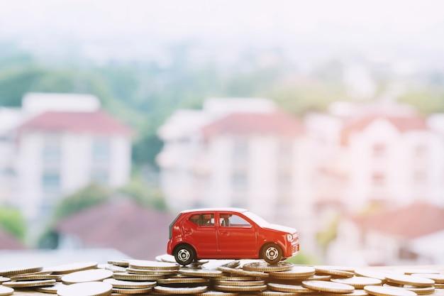 Pequeno carro vermelho sobre um monte de dinheiro empilhado moeda para empréstimos custa financiar o conceito com o efeito retro vintage dos tons do filtro, tons quentes.
