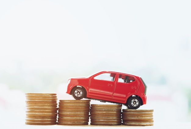 Pequeno carro vermelho sobre um monte de moedas empilhadas de dinheiro com a casa. para o conceito de financiamento de custos de empréstimos. com filtro tons efeito vintage retro, tons quentes.