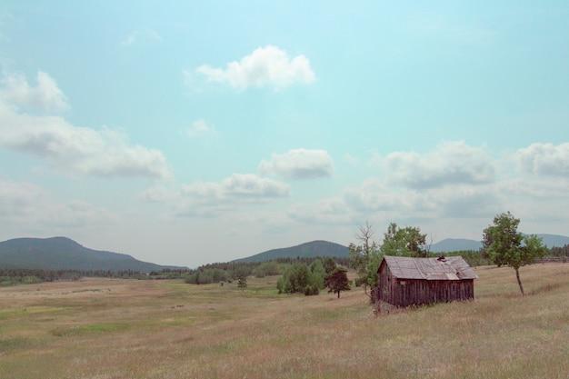 Pequeno celeiro de madeira construído em um grande campo