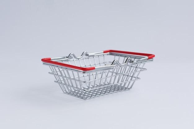 Pequeno cesto de compras de supermercado de metal, sobre um fundo branco.