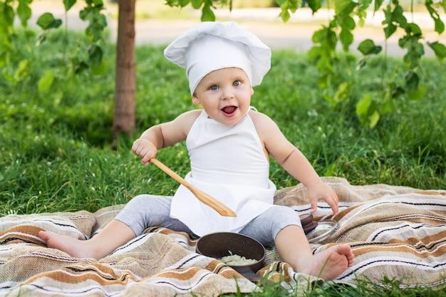 Pequeno chef cozinha e come macarrão em um piquenique ao ar livre