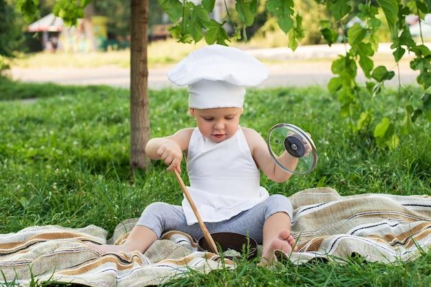 Pequeno chef cozinha macarrão em um piquenique ao ar livre. filho bonito em um terno de cozinheiro com panela e espátula de cozinha na parede verde da natureza