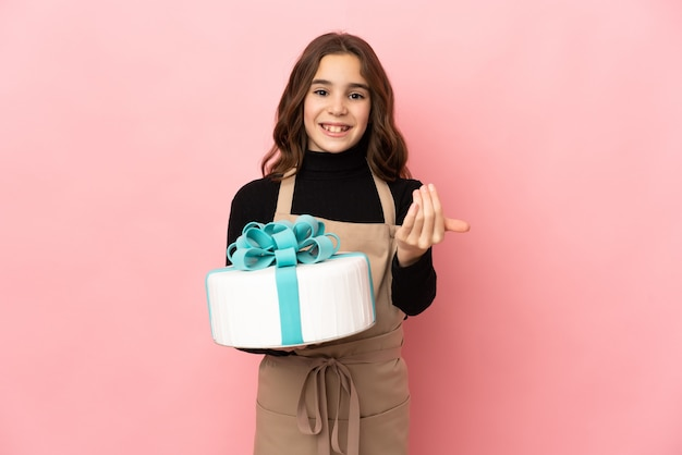Pequeno chef de pastelaria segurando um grande bolo isolado no fundo rosa, convidando para vir com a mão. feliz que você veio