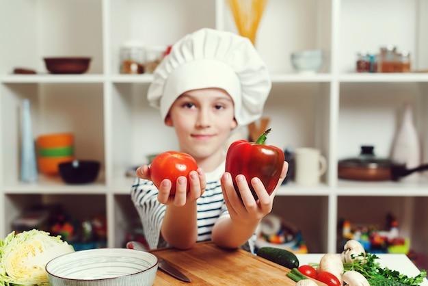 Pequeno chef segurando peper e tomate para cozinhar. menino bonito usando uniforme e chapéu de chef. cozinhar o conceito de comida. filho preparando comida saudável para o jantar em família. a criança quer ser chef profissional.