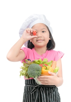 Pequeno chef sorridente segurando legumes mistura isolados no fundo branco, con alimentos saudáveis e limpos