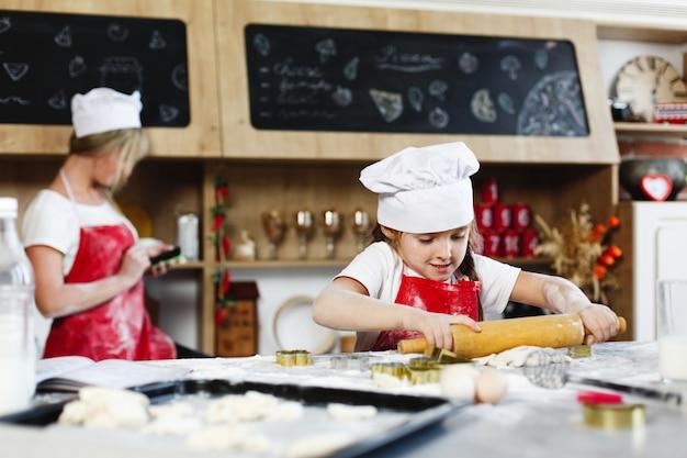Pequeno chefe. menina encantadora se diverte fazendo biscoitos de massa em uma cozinha aconchegante