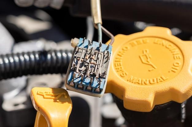 Pequeno componente eletrônico empoeirado em uma sonda de óleo e tampa de óleo sob o capô aberto de um carro. vista de perto em um dia ensolarado