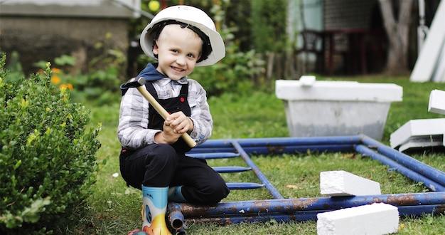 Pequeno construtor em um capacete branco com um martelo pequeno construtor ajudando os pais