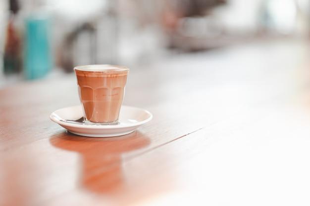 Pequeno copo de café com leite piccolo servido na mesa de madeira