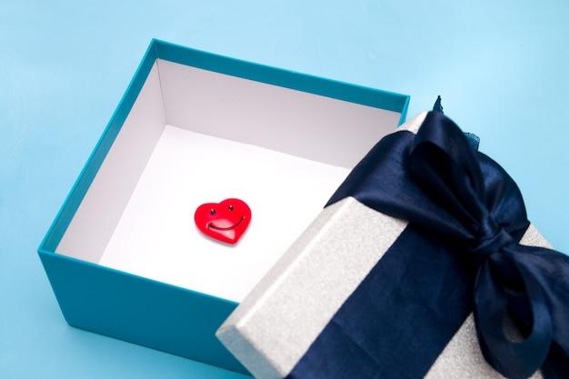 Pequeno coração sorridente em uma caixa de presente, fundo azul, close-up